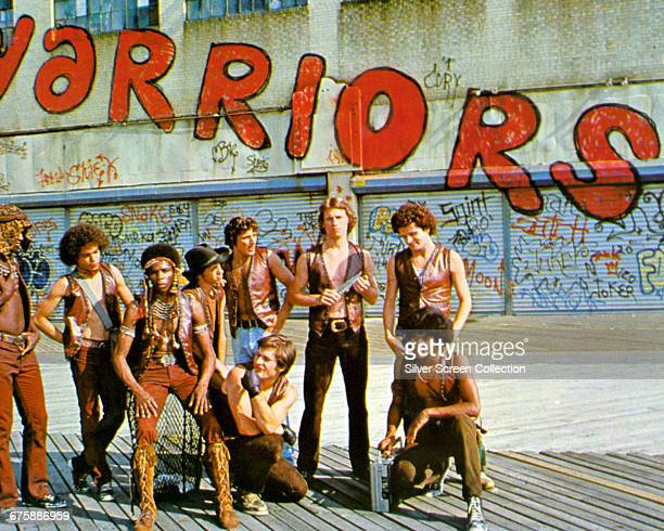View of cast members from the film 'The Warriors' as they pose in front of graffiticovered store fronts on the boardwalk at Coney Island New York New...