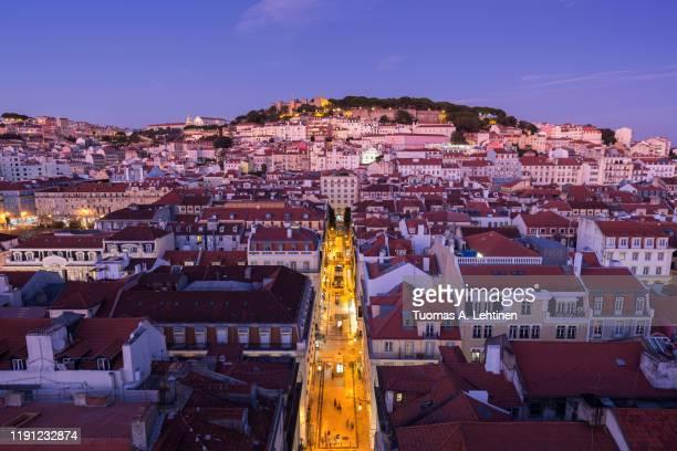 view of castelo de sao jorge, rua de santa justa street and alfama and baixa districts in lisbon, portugal, from above at dusk. - バイシャ ストックフォトと画像