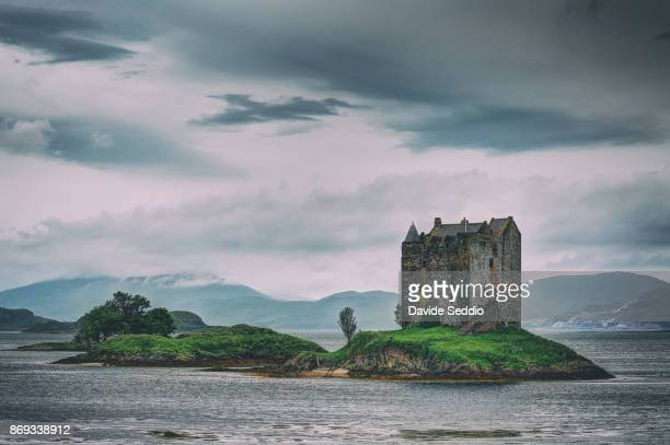 View of Castle Stalker rising from the waters of Loch Linnhe on a cloudy day