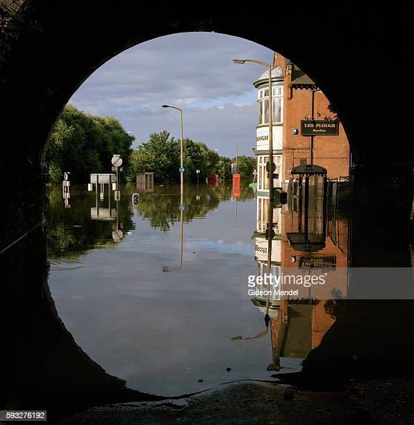 A view of Catcliffe Village showing one of the flooded streets reflected under the arch of an old disused railway bridge This was one of the...