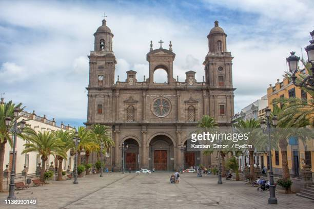 view of cathedral against cloudy sky - las palmas cathedral stock photos and pictures