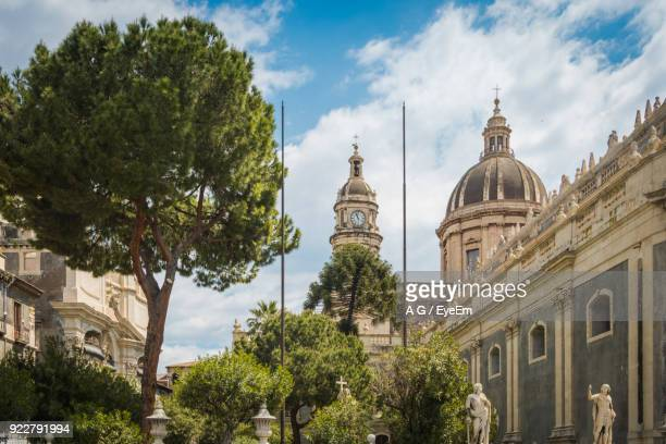 view of cathedral against cloudy sky - catania stock photos and pictures