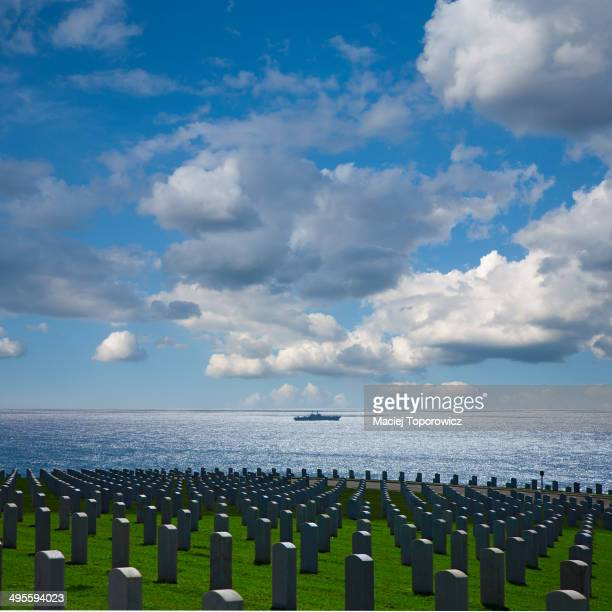 CONTENT] View of cemetery with a warship in a distance