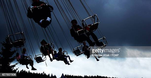 View of chain swing ride against cloudy sky