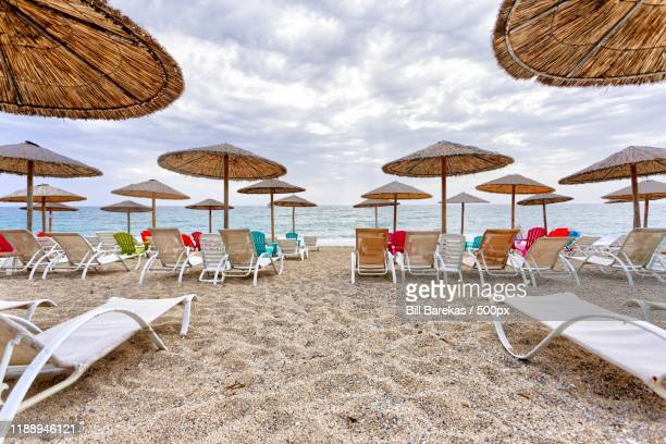 view of chairs and umbrellas on beach, preveza, epirus,  greece - epirus greece stock pictures, royalty-free photos & images