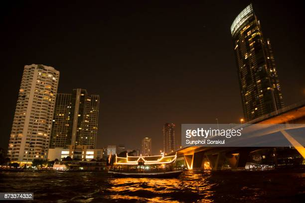 View of Chao Praya river at night time with skyscrapers surrounding Taksin bridge and lit boats travelling along river.