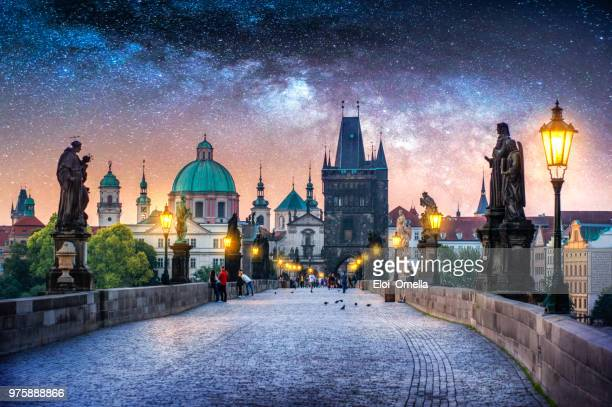 view of charles bridge in prague at night with milky way. czech republic - charles bridge stock photos and pictures