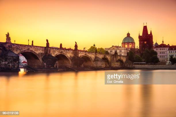 view of charles bridge in prague at sunrise. czech republic - charles bridge stock photos and pictures