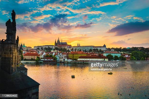 view of charles bridge in prague during sunset, river vltava czech republic. - bohemia czech republic stock pictures, royalty-free photos & images