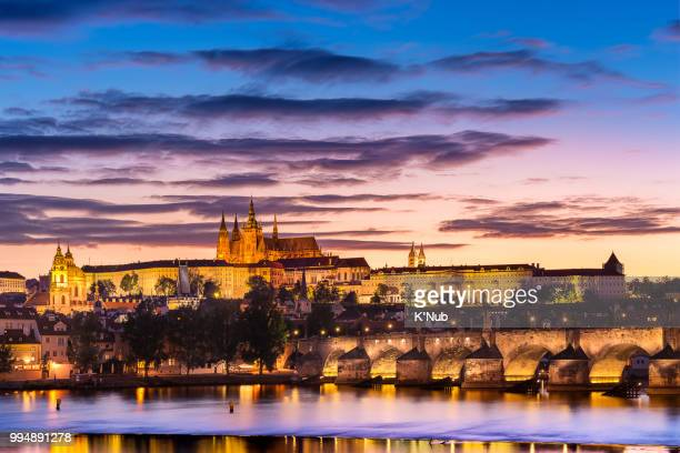 View of Charles bridge, St. Nicholas Church, and castle of St. Vitus Cathedral at Sunset time with reflection on water in river in Prague (Praha), Czech Republic, Europe, where is the most visiting place from tourist for travel