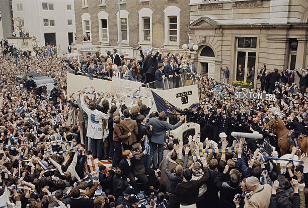 View of Chelsea Football Club team players standing on the top deck of an open top bus as they parade with the FA Cup trophy through the streets of...