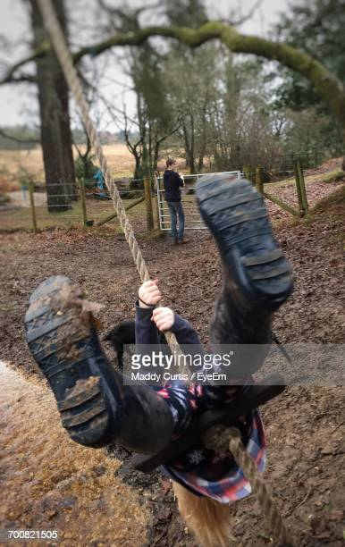 view of child on rope swing - teen soles stock photos and pictures