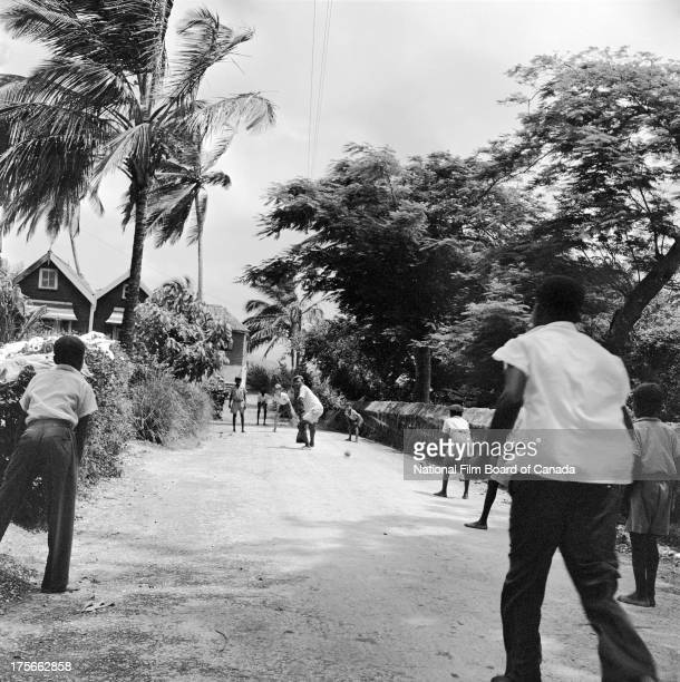 View of children playing cricket in a street in Port of Spain, Trinidad, Trinidad and Tobago, August 1956. Photo taken during the National Film Board...