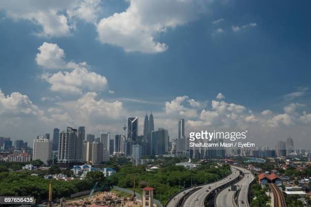 view of city against cloudy sky - shaifulzamri stock pictures, royalty-free photos & images