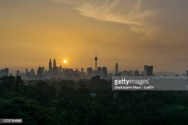 view of city at sunset - shaifulzamri stock-fotos und bilder