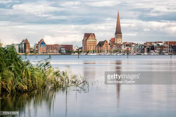 view of city at waterfront against cloudy sky - rostock stock pictures, royalty-free photos & images