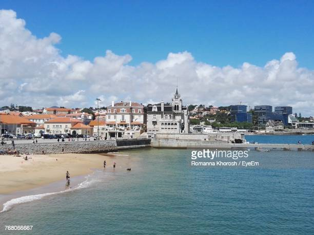 view of city at waterfront against cloudy sky - cascais stock photos and pictures