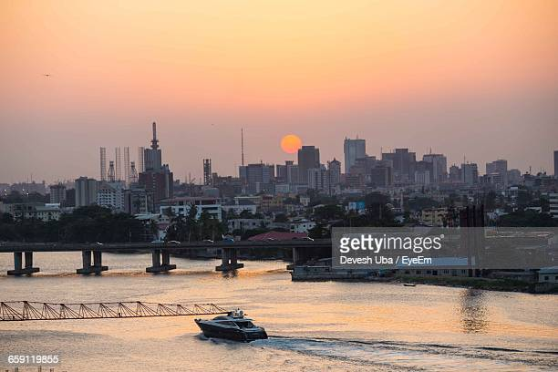 view of city at waterfront during sunset - nigeria stock pictures, royalty-free photos & images