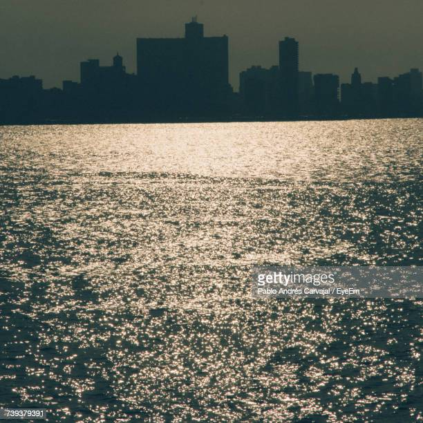 view of city at waterfront during sunset - carvajal stock photos and pictures