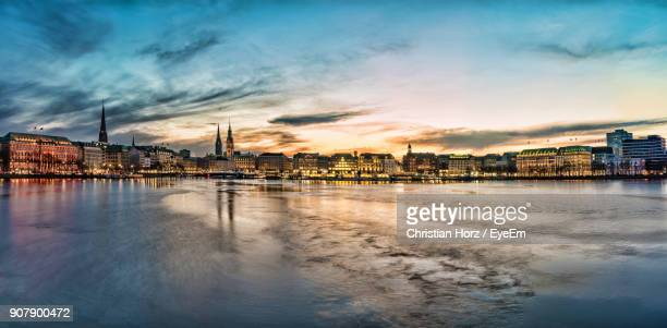 view of city at waterfront during sunset - hamburg germany stock pictures, royalty-free photos & images