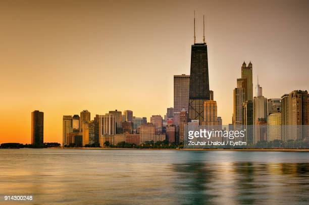 view of city at waterfront during sunset - chicago illinois fotografías e imágenes de stock