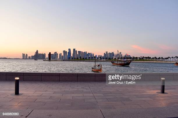 view of city at waterfront during sunset - doha stock photos and pictures