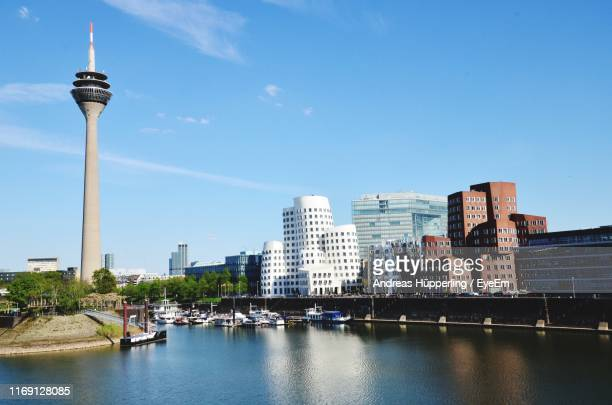 view of city buildings by river against sky - düsseldorf stock pictures, royalty-free photos & images