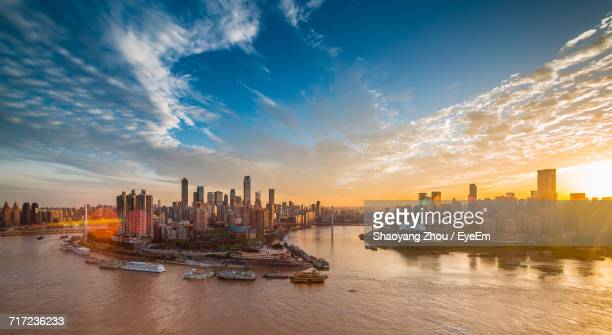 View Of City By River Against Sky During Sunset