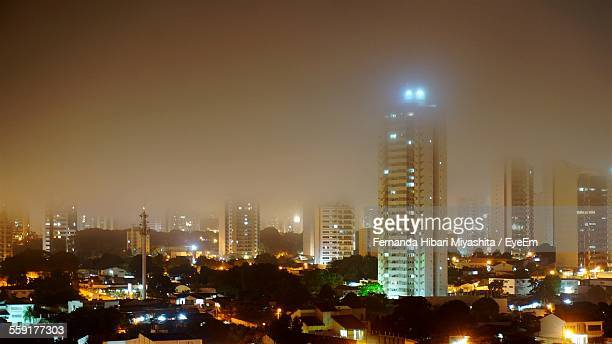 view of city lit up at night - cuiabá stock photos and pictures