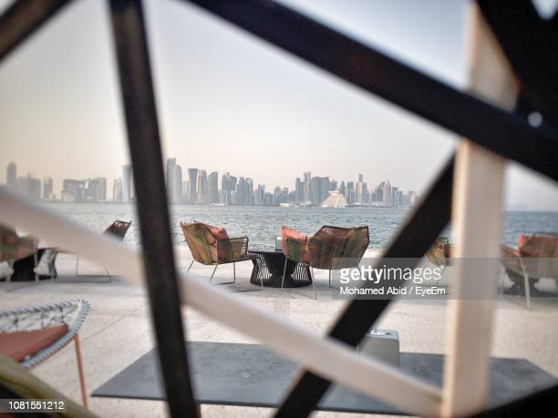 view of city seen through railing by sea against sky - doha stockfoto's en -beelden