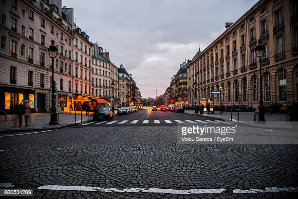 view of city street against cloudy sky - fluchtpunkt stock-fotos und bilder