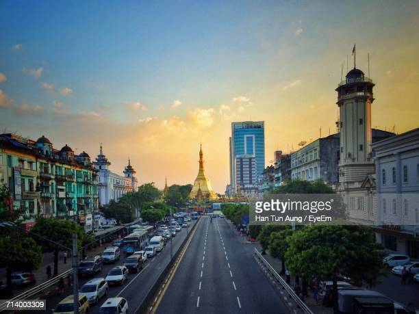 view of city street against cloudy sky - yangon stock pictures, royalty-free photos & images