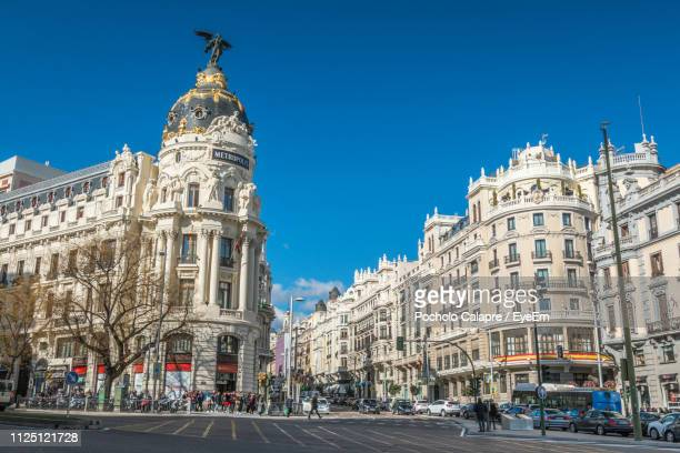 view of city street and buildings against blue sky - madrid stock-fotos und bilder