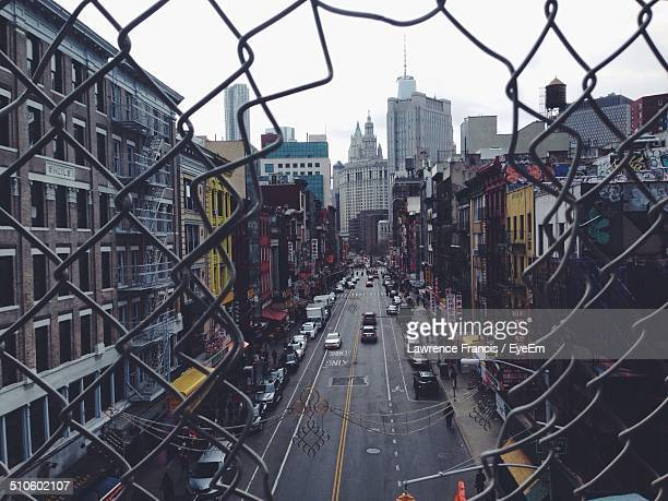View of city street through broken chainlink fence
