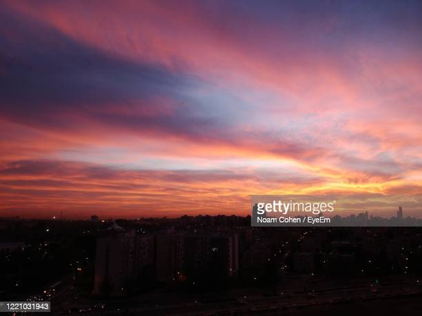 view of cityscape against cloudy sky during sunset - noam cohen stock pictures, royalty-free photos & images