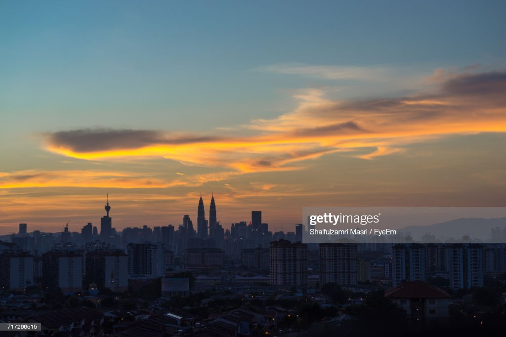 View Of Cityscape Against Cloudy Sky During Sunset : Stock Photo