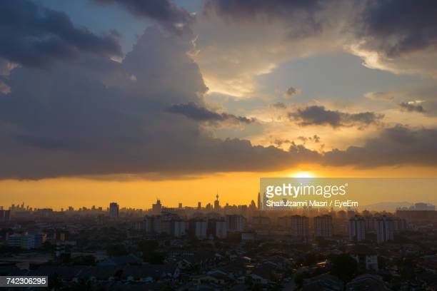 view of cityscape against cloudy sky during sunset - shaifulzamri stock pictures, royalty-free photos & images