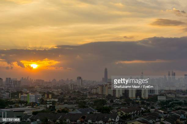 View Of Cityscape Against Cloudy Sky During Sunset
