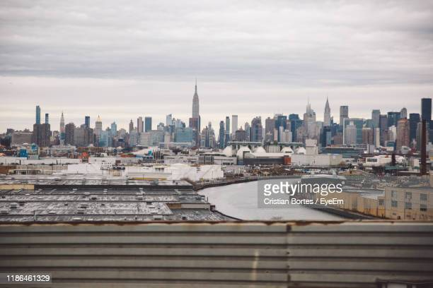view of cityscape against cloudy sky - bortes stock photos and pictures