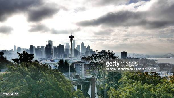 view of cityscape against cloudy sky - seattle stock-fotos und bilder