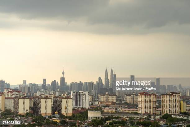 view of cityscape against cloudy sky - shaifulzamri stock pictures, royalty-free photos & images