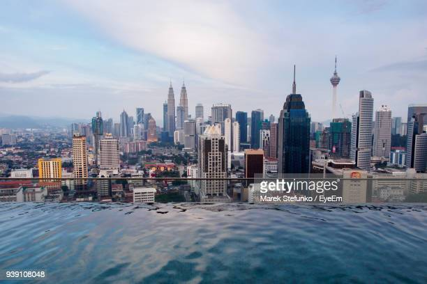 view of cityscape against cloudy sky - marek stefunko stock photos and pictures