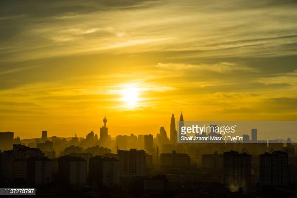 view of cityscape against dramatic sky - shaifulzamri foto e immagini stock