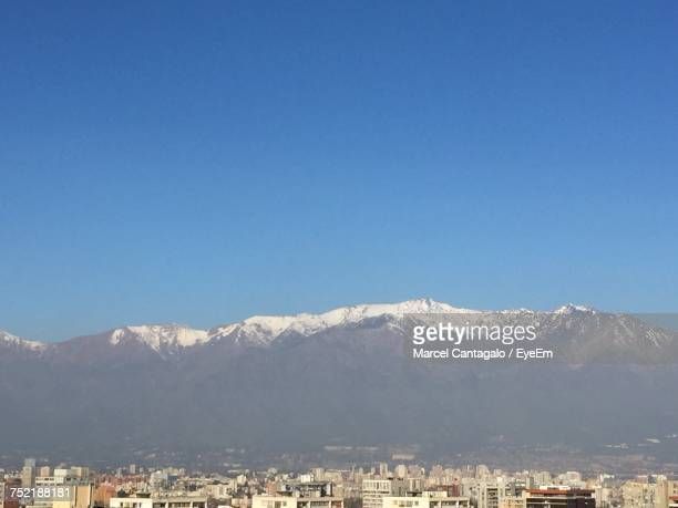 View Of Cityscape And Mountains Against Clear Blue Sky