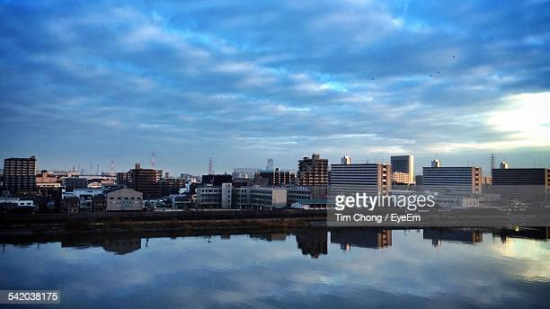 View Of Cityscape By Calm River Against Cloudy Sky