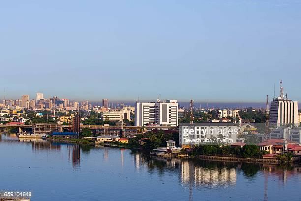 view of cityscape by river against sky - nigeria stock pictures, royalty-free photos & images