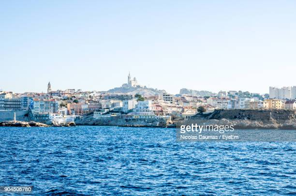 view of cityscape by sea against clear sky - marseille photos et images de collection