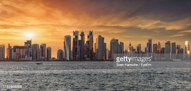 view of cityscape by sea against sky during sunset - qatar photos et images de collection