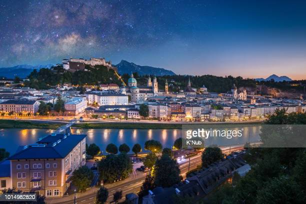 view of cityscape of salzburg cathedral, fortress hohensalzburg, and old castle in center of old town with river and road along the river at sunset time with milky way in salzburg, austria, europe and also view of snow on alps mountain in background - salzburger land stock pictures, royalty-free photos & images