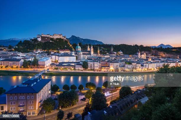 View of cityscape of Salzburg Cathedral, Fortress Hohensalzburg, and old castle in old town, famous landmark for travel from tourist at sunset time in Salzburg, Austria, Europe with snow on alps mountain in background